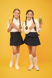 Healthy nutrition. Schoolgirls holding juice bottle on yellow background. Quenching thirst during school time. Thirst and dehydration. Healthy snack fruit smoothie. Smoothie detox. Yummy smoothie