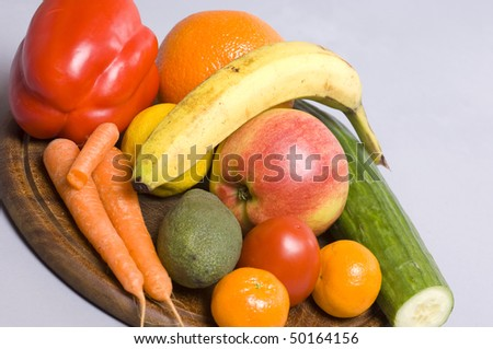 Healthy nutrition with different fruits and vegetables on a wooden plate for a long and powerfull life.