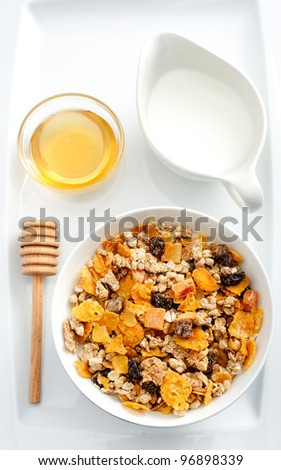 Healthy nutritious bowl of cereal with honey and milk - stock photo