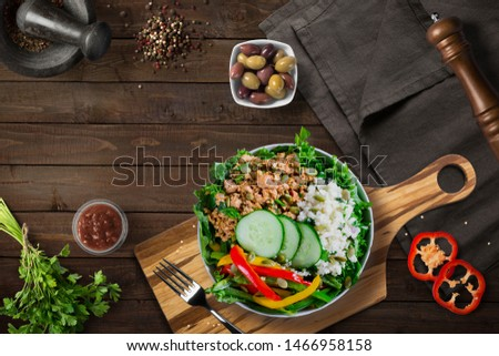 Healthy nutritious keto paleo lunch or dinner - ground turkey taco bowl with cauliflower rice, bell peppers, cucumber and pumpkin seeds and olives and fresh salsa. Flat lay. Wooden background table.
