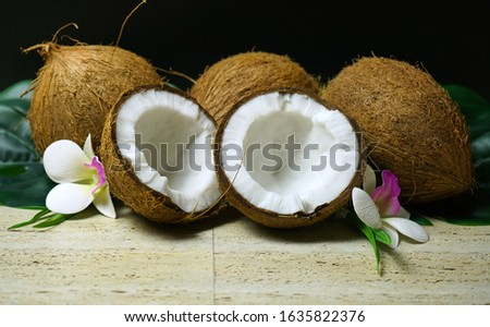 Healthy nutritious natural coconut with a vast range of dietary and cosmetic advantages and uses, shown here with coconuts and frangipani flowers spotlighted against a black background.