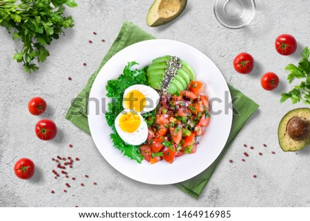 Healthy nutritious paleo keto breakfast - kale with boiled egg, fresh cherry tomato salsa and avocado with chia and hemp seeds on white plate on light background. Flat lay.