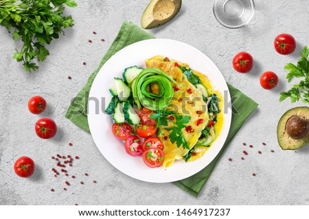 Healthy nutritious paleo keto breakfast. Omelette with zucchini and swiss chard topped with red pepper flakes, served with fresh cherry tomatoes, cucumbers and chives on white plate. Flat lay.