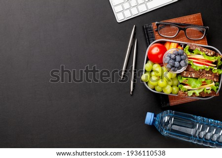 Healthy office lunch box with sandwich and fresh vegetables, water bottle, nuts and fruits on desk. Top view flat lay with copy space