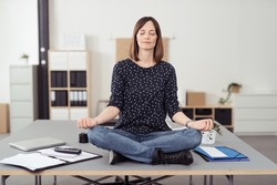 Healthy Office Woman Sitting on the Table at the Boardroom While Doing Yoga Exercise In Front of the Camera.