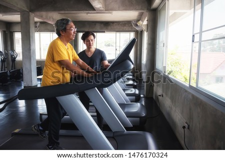Healthy old man running on treadmill while his grandson coaching him at fitness gym. family in sport center to exercise or workout  for good health. Nephew take care of grandfather. #1476170324