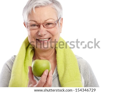 Healthy old woman holding green apple, smiling, towel around neck.