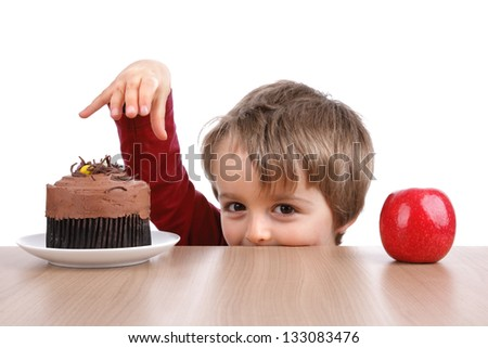 Healthy or unhealthy eating little boy choosing between a cake or an apple