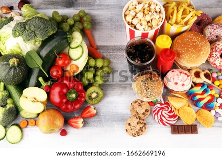 healthy or unhealthy food. Concept photo of healthy and unhealthy food. Fruits and vegetables vs donuts,sweets and burgers on table Stock photo ©