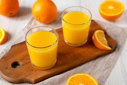 Healthy Orange Juice on a rustic board on a white wooden background, side view.