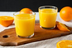 Healthy Orange Juice on a rustic board, side view. Close-up.