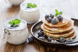 Healthy organic blueberry smoothie in glass jar and buttermilk pancakes with fresh berries on rustic wooden table