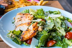 Healthy organic Chicken Caesar Salad. Caesar Salad with grilled chicken on plate. Grilled chicken breasts and fresh vegetables in plate. Caesar Salad with grilled chicken on white plate.