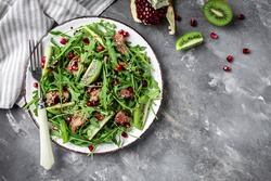 Healthy organic Chicken liverSalad. Salad with grilled chicken chicken liver, kiwi and pomegranate, arugula in plate. Healthy food. Flat lay. Top view.