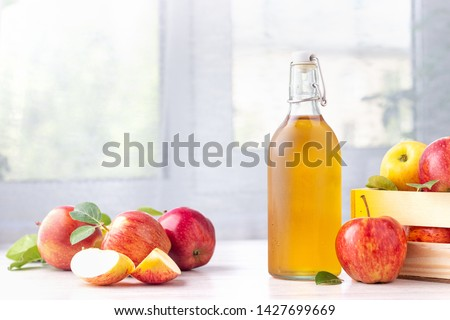 Healthy organic food. Apple cider vinegar in glass bottle and fresh red apples on a light background. Foto stock ©