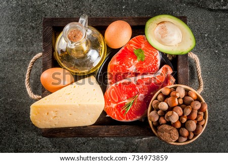 Healthy organic food. Products with healthy fats. Omega 3, omega 6. Ingredients and products: trout (salmon), olive oil, avocado, nuts, cheese, eggs. On dark stone table. Copy space top view #734973859