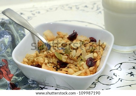 Healthy organic homemade granola in a bowl on an ornate serving tray with a glass of milk and a napkin