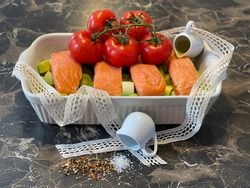 Healthy oven dish of salmon, leek, tomatoes, olive oil in a small pitcher, fleur de sel and tasty mixed pepper with a decoration of lace ribbon on a brown marble look table.