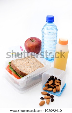 Healthy packed lunch with wholemeal sandwich, apple, dried fruit, nuts and yoghurt isolated on white