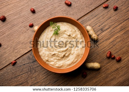 Healthy Peanut chutney made using Groundnut / Shengdana or mungfali. served in a small bowl with raw whole. Selective focus
