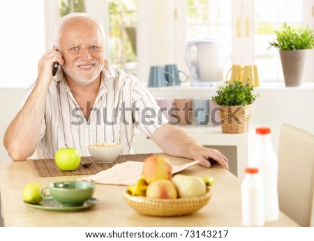 Healthy pensioner using cellphone at breakfast table, smiling at camera.?