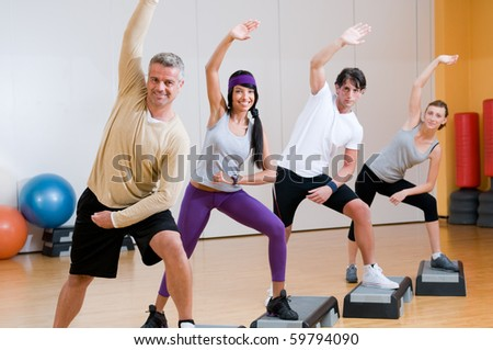 Healthy people doing aerobic exercises together at gym