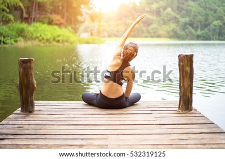 Healthy person woman lifestyle balanced body practicing meditate and energy fit yoga relax and spirit on the bridge in morning the nature.  Healthy Concept  #532319125