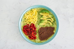 healthy plant-based food recipes concept, vegan version fo the viral layered tortilla wrap hack with red peppers grated dairy-free cheese avocado and refried beans