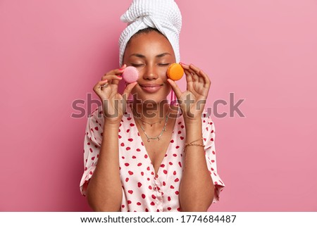 Healthy pleased woman with dark skin closes eyes, holds two sweet macaroons, closes eyes with pleasure, breaks diet and eats junk food, wears dressing gown and towel, isolated on pink background
