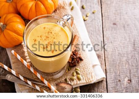 Healthy pumpkin smoothie in big mugs on rustic background