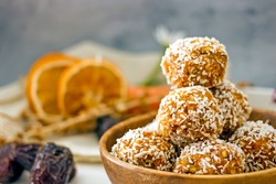 Healthy raw energy balls. Candy vegan balls of dates, coconut pulp, carrots in a wooden bowl are laid out in the shape of a pyramid. Top view, concept of useful home-made candies without sugar