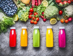 Healthy red, orange, green, yellow and pink Smoothies  and juices in Bottles on grey concrete background with fresh organic vegetables , fruits and berries ingredients, top view