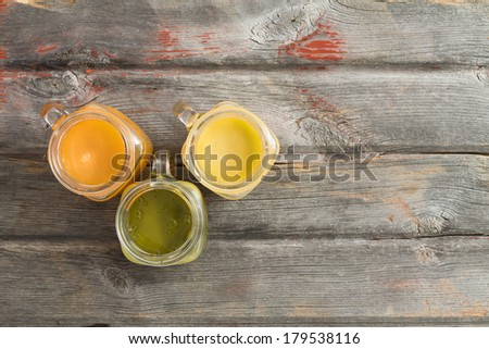 Healthy refreshing tropical fruit juice served in three glass jugs on an old weathered wooden picnic table including mango, orange and kiwifruit blends, with copy space