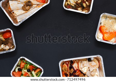Healthy restaurant food delivery background with copy space. Mockup for menu, foil containers with meals on black