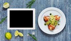 Healthy restaurant food. Seafood dish top view with copy space at tablet. Menu, cooking site, recipe template. Ratatoille with cheese and shrimp top view, flat lay with copyspace at blue rustic wood.