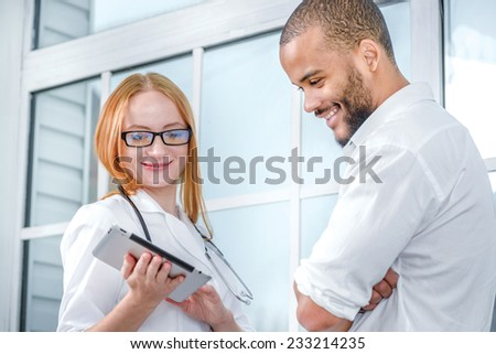 Healthy results. Confident and smiling doctor and patient with a smile looking at the tablet and study the results of medical research on the tablet