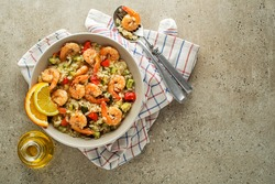 Healthy risotto meal with grilled shrimps and vegetables on grey background. Grilled prawns. Healthy food. Seafood.
