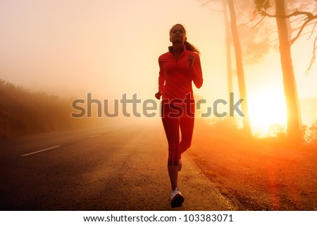 Stock Photo Healthy running runner woman early morning sunrise workout on misty mountain road workout jog. sunflare through the mist gives atmospheric feel and depth to these fitness images