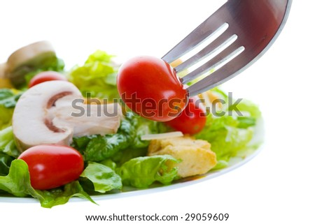 healthy salad appetizer with a cherry tomato on a fork