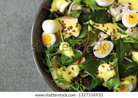 Healthy salad bowl. Salad with chicken breast, quail eggs, salad mix, flax seeds, yoghurt sauce with mustard. Keto diet. Pegan diet. Paleo diet. Keto dinner or lunch.