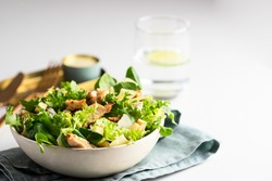 Healthy salad bowl with  different  lettuce, chicken, cheese and croutons  on the table in reataurant.