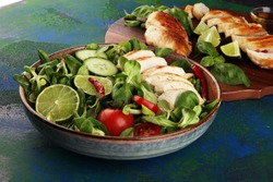 Healthy salad bowl with tomatoes, chicken and mixed greens, lettuce. Food and health bowl with cucumber and lemon