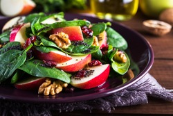 Healthy salad plate with apple, dried cranberry, walnut, spinach and poppy seed dressing on wooden background close up. Food and health. Clean eating.