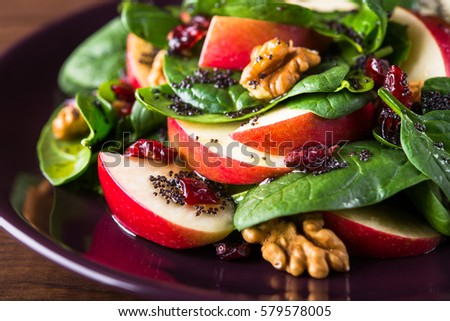 Shutterstock Healthy salad plate with apple, dried cranberry, walnut, spinach and poppy seed dressing on wooden background close up. Healthy food. Clean eating.
