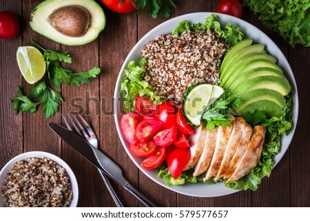 Healthy salad plate with quinoa, cherry tomatoes, chicken, avocado, lime and mixed greens, lettuce, parsley on wooden background top view. Food and health. Superfood meal. Stock photo ©