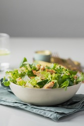 Healthy salad with  different lettuce, croutons,cheese,  chicken and dressing with especial sauce. Caesar salad in the white plate served with glass water and gold cutlery on the restaurant table.