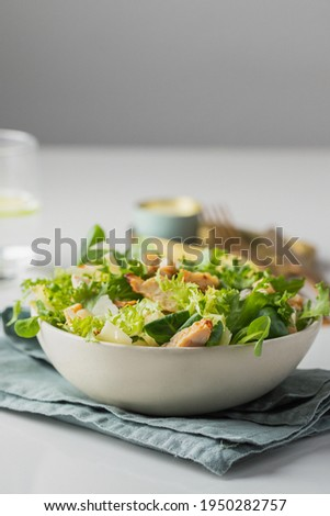 Healthy salad with  different lettuce, croutons,cheese,  chicken and dressing with especial sauce. Caesar salad in the white plate served with glass water and gold cutlery on the restaurant table. ストックフォト ©