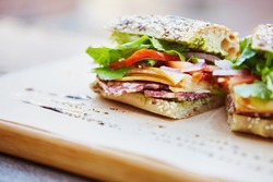 Healthy sandwich made of a fresh seeded roll, cut in half to display tasty ingredients of salami, tomato, lettuce and chess, presented on a wooden board