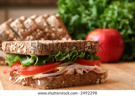 Healthy sandwich made with whole grain bread, lettuce, tomato, cheese, and roasted turkey slices. - stock photo