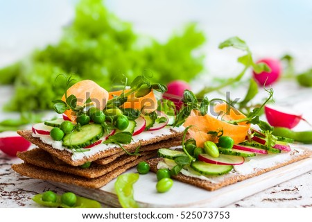 Healthy sandwiches with soft cheese and raw spring vegetables on crisp rye bread.